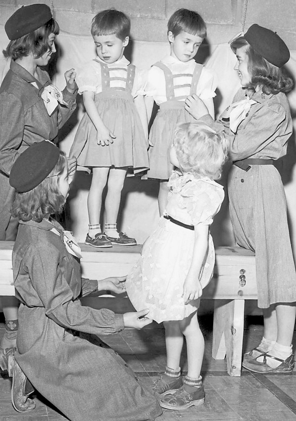 Girl Scouts from Troop 1 give a few final tweaks to the dresses the m odels wear for the Girl Scout Fashion show held at the Hermon gymnasium in 1955. Taking part are (from left, front row) Deidra Bell and Peggy Wing, 5. In second row are Judy Andrews, Katherine and Karen Rich, both age 4, and Nancy Scanlin.