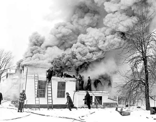 A fire resulting from an exploding oil burner caused an estimated $20,000 damage of the paint shop of George Betterley, 16 North St., Bangor, at 8 a.m. on Saturday, Dec. 31, 1955. The firemen made quick work to extinguish the blaze, even though they were hampered by the thick, rolling smoke shown above, and the bitter cold. There were no injuries.