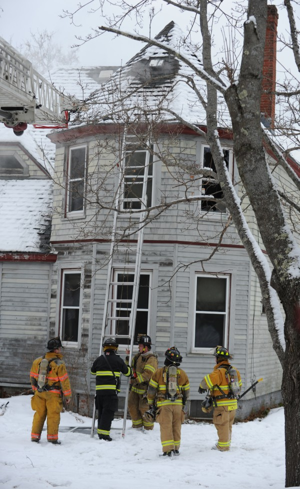 Firefighters set up ladders at 40 Main Road South in Hampden on Monday. Crews from Hampden, Bangor, Hermon, Newburgh and Winterport responded. Phillipa Gilmore along with her 13-year-old daughter escaped after spotting flames hear a wood stove on the first floor on Monday afternoon.