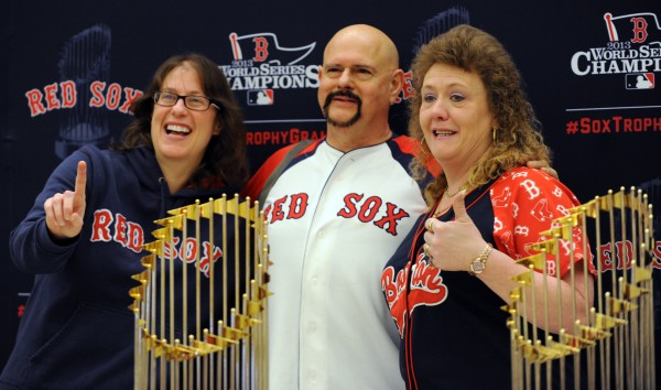 Lori, Stephen and Marie Huckabey pose for a photo with all three of the Red Sox World Series trophies at the Cross Insurance Center on Sunday.