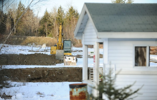 An excavator is used to increase the size of earth berms at the Orrington Rod and Gun club in Orrington on Tuesday.