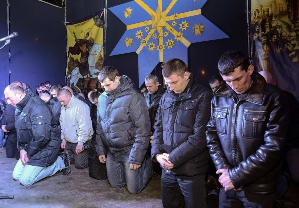 Local riot police kneel as they apologize to Lviv residents for taking part in an operation against anti-government protesters in Kiev but said that they did not beat protesters, during a rally in central Lviv February 24, 2014. Ukraine's fugitive president was indicted for &quotmass murder&quot on Monday over the shooting of demonstrators as new leaders in Kiev sought urgent Western aid to make up for a loss of funding from Russia, which is angry at the overthrow of its ally.