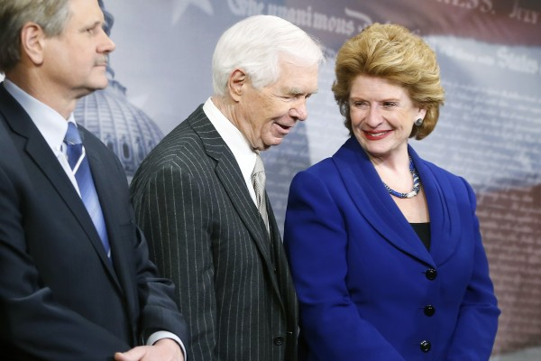 U.S. Senate Agriculture Committee Chairman Debbie Stabenow (D-MI) smiles with ranking member Senator Thad Cochrane (R-MI), center, at a news conference after the final passage of the Farm Bill at the U.S. Capitol in Washington, February 4, 2014.