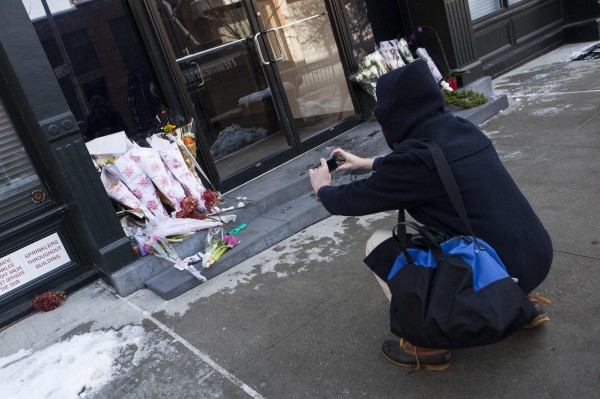 A passerby takes photographs of a makeshift memorial for actor Philip Seymour Hoffman in front of his apartment building in the Manhattan borough of New York, February 4, 2014.