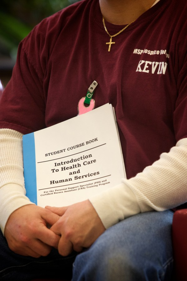 Hospice volunteer Kevin Knight, an inmate at the Maine State Prison in Warren, holds a training manual Friday.
