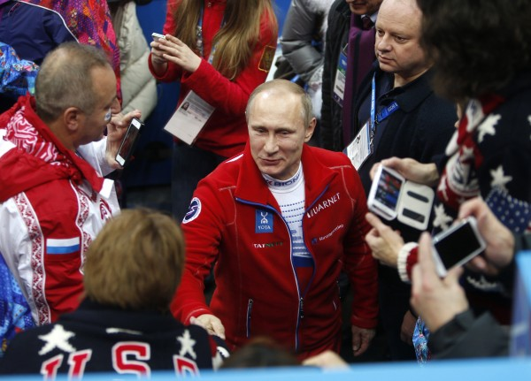 Russian President Vladimir Putin shakes hands with a USA coach after the conclusion of the team figure skating during the Winter Olympics at the Iceberg Skating Palace in Sochi, Russia, on Sunday, Feb. 9, 2014.