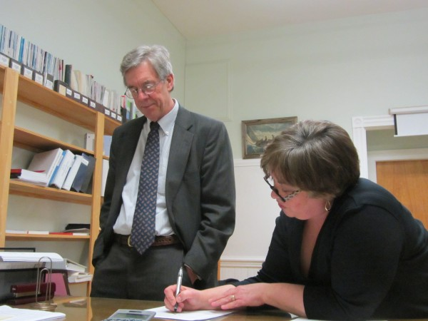 Michael Wilhelm prepares to sign a contract with Regional School Unit 13 Board Chairwoman Esther &quotTess&quot Kilgour on Tuesday night to serve as the Rockland area school district's interim superintendent through May 24.