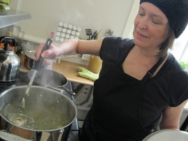Courtney Sanders stirs a pot of Spinach and Arborio Rice Soup, one of many changing soup options at her Belfast business, Daily Soup.