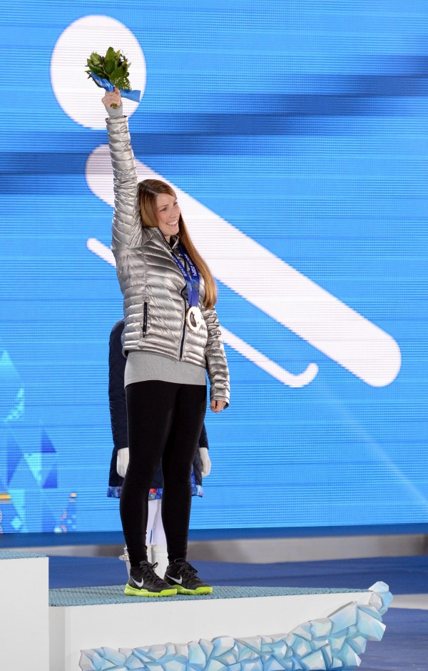 Erin Hamlin (USA) waves to the crowd after receiving her bronze medal during the medal ceremony for the women's singles luge during the Sochi 2014 Olympic Winter Games at the Medals Plaza.