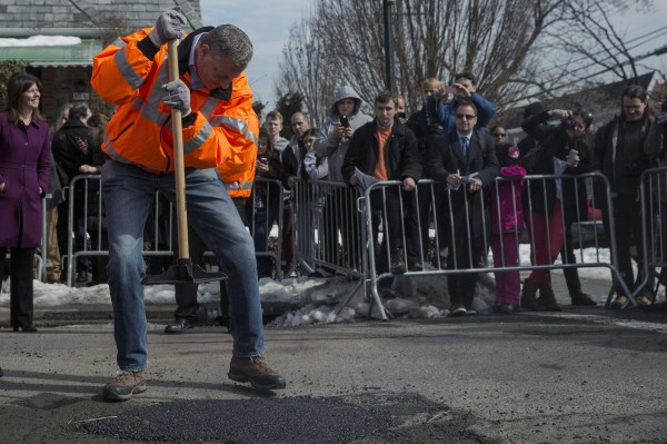 New York Mayor Bill de Blasio finishes filling a pothole in the Maspeth section of Queens, N.Y., on Thursday.