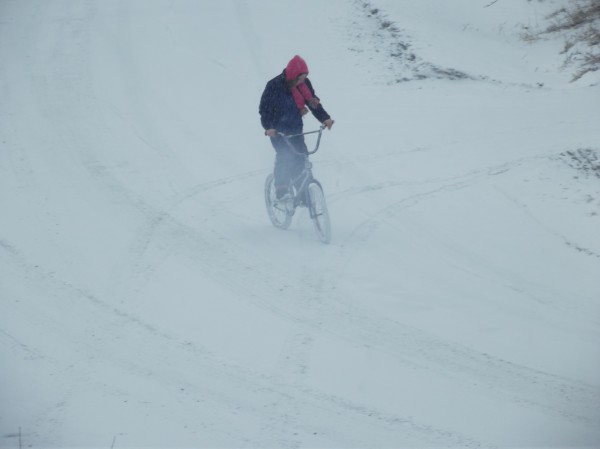 A Machias youth, undeterred by the winter storm that arrived Thursday afternoon, rides a bicycle on a snow-covered neighborhood street.