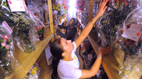 Asiah Hinckley (foreground) and Nich Dow look for bouquets of flowers in one of the coolers at Bangor Floral on Thursday. Phil Fredrick, owner of the shop, said that Valentine's Day is by far the busiest day for the shop. He hires 12 extra people and said they do about three months' work in three days.