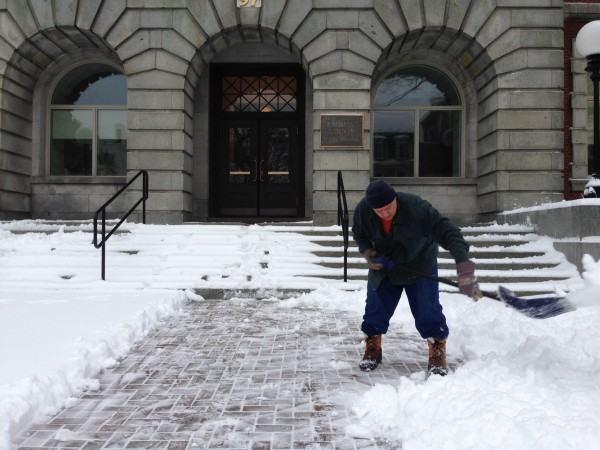 Shawn Bowman of Corinth shovels out the walk at the Penobscot Judical Center on Friday morning after a storm dumped several inches of snow and rain throughout Bangor. Bowman is serving time at the Penobscot County Jail and was shoveling as part of his work detail.