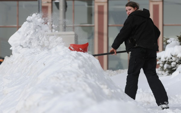 Allison Gibbs clears the sidewalk along Water Street in downtown Bangor on Sunday morning.