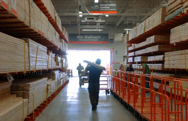 A customer carries lumber at The Home Depot's Bangor store in this file photo. The Home Depot plans to hire 450 hourly employees in Maine in time for the busy spring season.