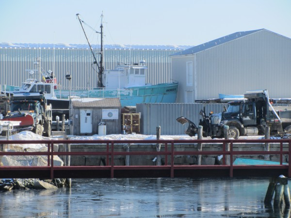 Rockland public works vehicle are at the city's fish pier Tuesday where snow is dumped after storms. The city council is debating whether to end that practice.