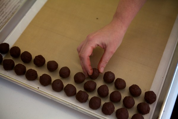 Hannah Smith rolls ganache -- the creamy center of a truffle -- in Laura Rudy's kitchen in Standish on Thursday. Rudy has been making a name for herself with her Maine beer inspired truffles.