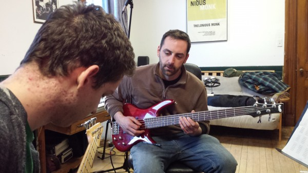 Kelly Bryand (right) gives a bass guitar lesson to Wolf Mullen (left), 17, of Sullivan, at Maine Academy of Modern Music studio in Machias.
