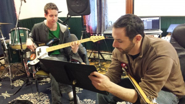 Kelly Bryand (right) makes notes for bass guitar student Wolf Mullen (left), 17, of Sullivan, at Maine Academy of Modern Music studio in Machias.