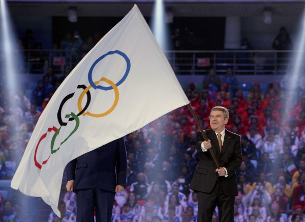 International Olympic Committee President Thomas Bach (right) waves the Olympic flag next to Sochi Mayor Anatoliy Pakhomov during the closing ceremony for the Sochi 2014 Winter Olympics on Sunday.
