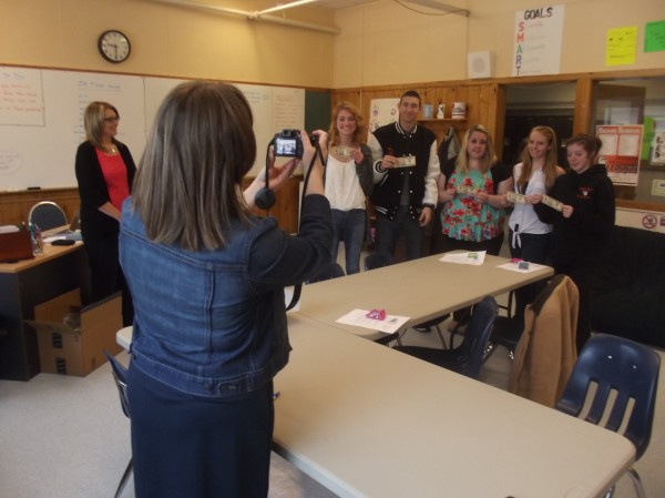 Christy Alley snaps a photograph of her Machias Memorial High School students, each with a $10 bill, while Lanette Pottle looks on. Pottle provided each student with $10 to 'pay it forward' and help someone else.