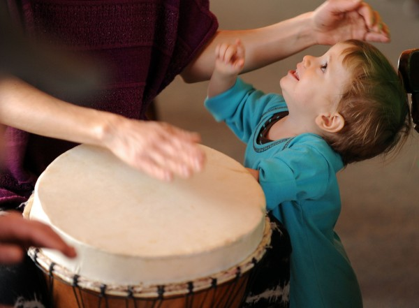 Astrea Charlett of Southwest Harbor plays a djembe as her 18-month-old son River begs her attention during a West African drumming workshop at Common Good Soup Kitchen in Southwest Harbor on Sunday Feb. 9, 2014.