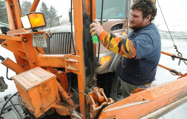 Ben Springer, a driver with the Maine DOT, sprays lubricant on the wing-plow tower of one of the plow trucks at the Hogan Road Maintenance Lot in Bangor in this February 2011 file photo.