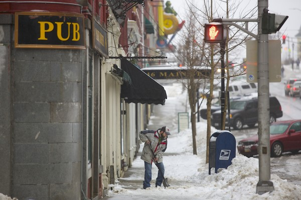 A man shovels snow downtown Bangor, Feb. 14, 2014.