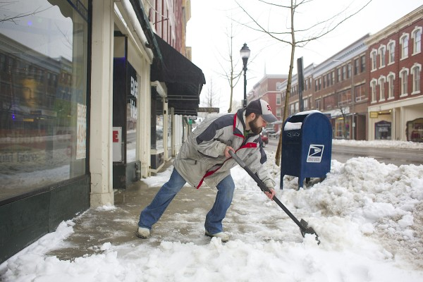 PJ Bailey shovels snow in front of Edge Video on Friday morning in Bangor.