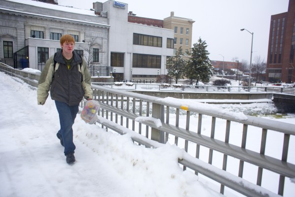Elija Mazza carries flowers to deliver to his girlfriend on Valentine's Day in Bangor. A storm that brought several inches of snow Thursday into Friday morning mixed with rain, creating slush and icy conditions throughout the Bangor area.