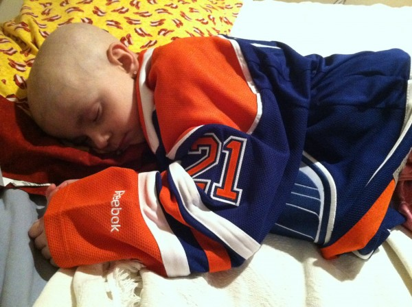 Maggie Rudnicki, a Levant child who is fighting Diamond Blackfan anemia, a rare genetic blood disorder, naps in a hockey jersey given to her by Andrew Ference, a former Boston Bruins player now captain of the Edmonton Oilers. The little girl and the pro hockey player have formed a strong bond after meeting at a Bruins game last year.