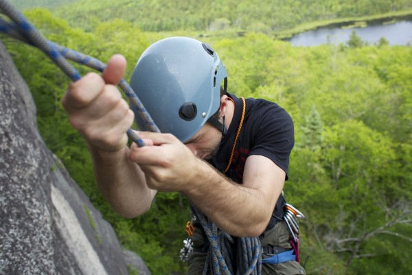 Jared Garfield, manager of rental equipment and repairs at the Maine Bound Adventure Center, switches positions at an anchor and belaying point on the 5.7+ route Highlander at Eagle Bluff in Clifton.