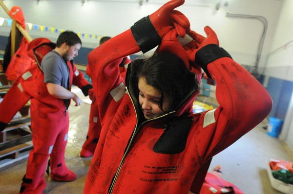 Logan Eaton struggles to get into a cold water survival suit at Maine Maritime Academy in Castine on Saturday. The students are from Deer Isle-Stonington High School and are enrolled in the Marine Studies Pathway program, which blends academic classes with research experience and specific skills for students interested in marine biology or a commercial fishing license.