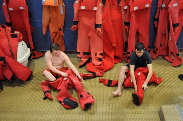 Michael Smith, left, and Cody Eaton race to get into cold-water survival suits at Maine Maritime Academy in Castine on Saturday.  The students are from Deer Isle-Stonington High School and are enrolled in the Marine Studies Pathway program which blends academic classes with research experience and specific skills for students interested in marine biology or a commercial fishing license.
