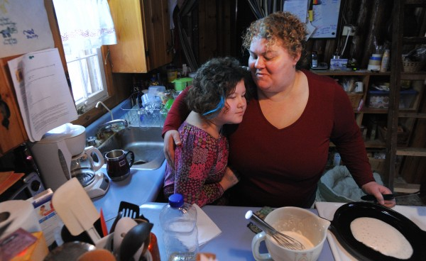 Liz Franck hugs her daughter Lucy Pearson while making pancakes for her on the morning of her 10th birthday at their Dedham home. Franck completed her undergraduate degree with help from the Parents as Scholars program and is now pursuing a master's degree in social work at the University of Maine.