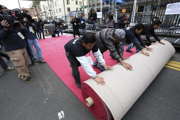 Workers roll out the Oscars red carpet during preparations for the 86th Annual Academy Awards in Hollywood, Calif., on Wednesday.