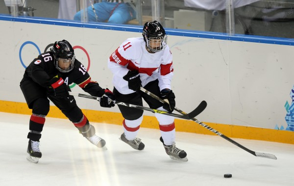 Switzerland's Angela Frautschi (right) battles for the puck with Canada forward Jayna Hefford during the women's ice hockey preliminary round game in the Sochi 2014 Olympic Winter Games at Shayba Arena on Saturday.
