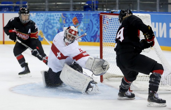 Canada's Marie-Philip Poulin (right) scores on Switzerland's goalie Florence Schelling during the second period of their women's ice hockey game at the 2014 Sochi Winter Olympics on Saturday.