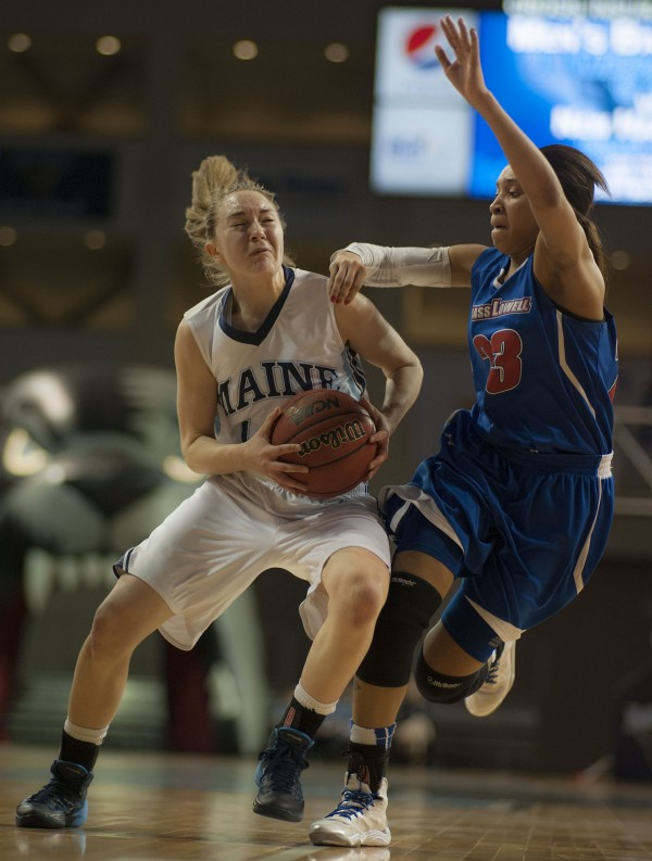Maine's Sigrid Koizar (42) drives past UMass Lowell's Jasmine McRoy (23) in the first half of their game at the Cross Insurance Center in Bangor on Wednesday night, Feb. 26, 2014. Maine won 84-65.
