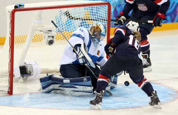 Finland goalkeeper Noora Raty (left) makes a save against USA forward Kelli Stack (center) during the women's ice hockey preliminary round game in the Sochi 2014 Olympic Winter Games on Saturday.