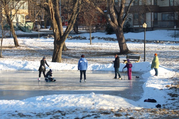 People enjoy the sunny weather at the ice rink at Broadway Park on Jan. 30, 2014, in Bangor.