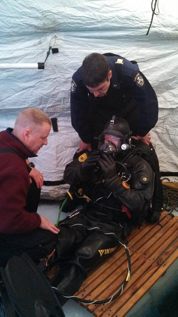 Maine State Police Dive Team Cmdr. Matt Grant  checks on Trooper Jeremiah Wesbrock before he enters the water of Moosehead Lake during training exercises this week.  Detective Gerry Coleman looks on.