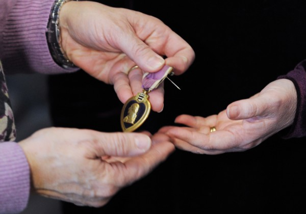 Monica Pollard (left) receives the Purple Heart medal that once belonged to her great-granduncle Frank Conroy from Sheila Bedi who found it in a box of items acquired at an auction. Bedi and her family drove from Vershire, Vt., to Pollard's Pittsfield home to return the lost Purple Heart medal.