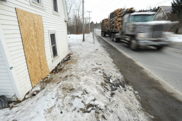 A truck loaded with logs rolls past a house at the intersection of Rt. 9 and Clewleyville road in Eddington. The house was struck by a SUV on Monday morning.
