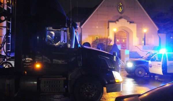 The driver of a tractor-trailer sits in the cab as police investigate an accident involving a pedestrian and his truck along South Main Street in Brewer on Sunday night. The pedestrian was taken to an area hospital.