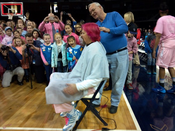 University of Maine women's basketball coach has his pink hair shaved of by Don Thomas of Center Beauty Parlor and Barber Shop after Sunday's victory over Binghamton at the Cross Insurance Center in Bangor. Barron dyed his hair and agreed to have it shaved to help generate support for UMaine's &quotPlay4Kay&quot initiative in support of the Kay Yow Cancer Fund.
