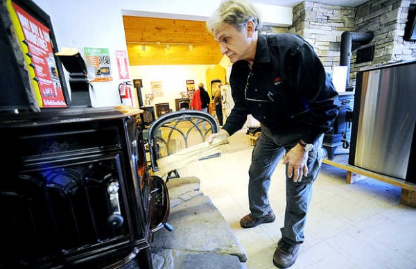 Gary Asselin feeds a log into a high-efficiency wood-burning Jotul stove at his Auburn store, Fireside Stove Shop, in November.