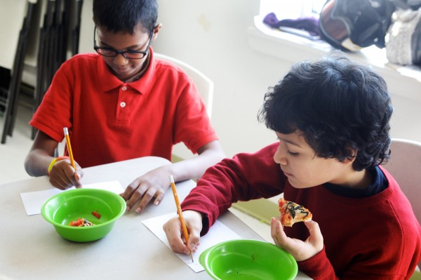 East End Community School fourth graders Ali Djana (left) and Nazar Salman record their impressions while trying seaweed pizza in Portland on Wednesday. As part of a program to expand offerings of locally sourced food in the school's cafeteria, students are given weekly chances to taste test new dishes and decide whether the cuisine should be added to the hot lunch menu.