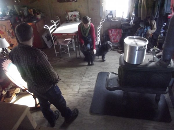 The Gileses rely on a wood stove for heat; the pot on the stove heats water for washing and bathing. Portions of the home, interior and exterior, are unfinished.