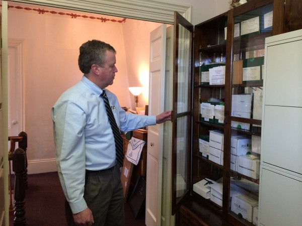James Fernald, a fifth-generation funeral director who works at Brookings-Smith Funeral Home in Bangor, opens a cabinet used to store urns containing unclaimed remains. The funeral home has 82 unclaimed remains that date back to 1951.